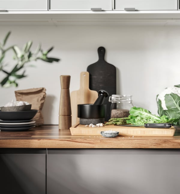 Herbs and spices are prepared using an AEDELSTEN Pestle and mortar and chopping board in a white kitchen