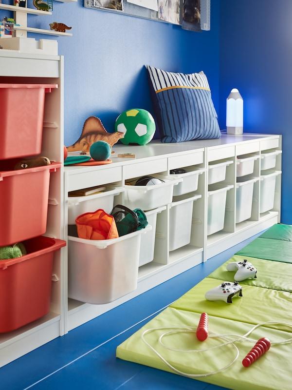En blå væg med en hvid legetøjsopbevaringsløsning, en blå og orange pude, en legetøjsdinosaur og en grøn legemåtte på gulvet.