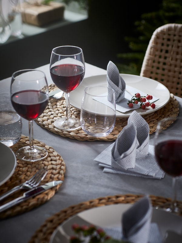 A decorated table set with braided SOARÉ place mats, folded napkins, beige FÄRGKLAR plates and drinks in SVALKA wine glasses.