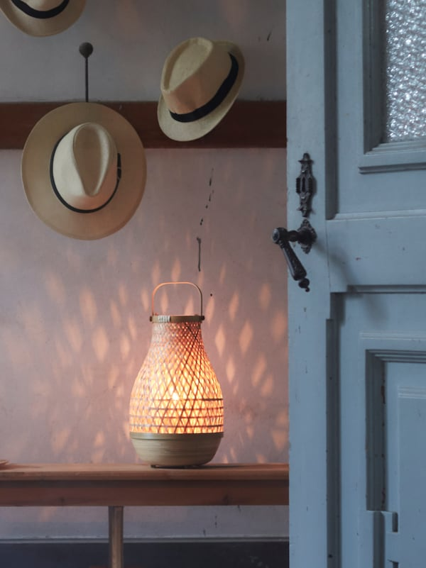 Two hats hanging on a wall above a lamp with a handle, the light from the lamp creating a design effect on the wall.