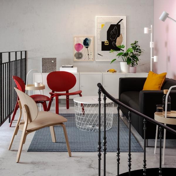 مساحة استرخاء بها صوفا سوداء وكراسي استرخاء حمراء وعمل فني ملون على الحائط وطاولة تخزين بيضاء.