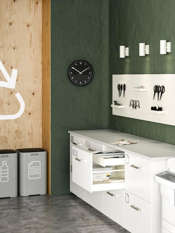 Una stanza per le fotocopie con cassettiere bianche, pannelli portaoggetti bianchi, faretti bianchi, secchi per la raccolta differenziata e un orologio da parete nero - IKEA