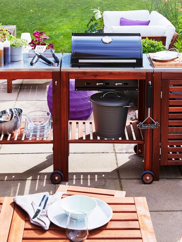 شوايةفحم مع عربة وخزانة من خشب السنطفي فناءأمامطاولةطعامخارجية.