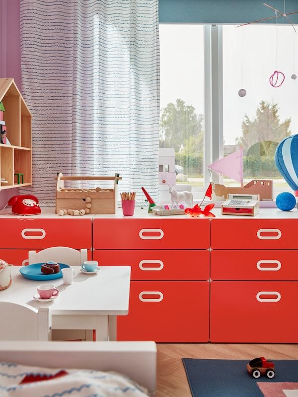 窗前放着红色的STUVA 斯多瓦/FRITIDS 福利蒂德斯 三斗抽屉柜,上面放着各式玩具,例如一台电话。