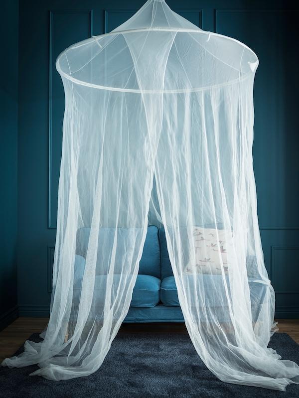 Într-o încăpere albastră, o plasă de baldachin cade peste o canapea mică albastră.
