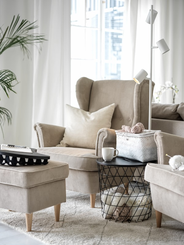 A beige STRANDMON wing chair with a matching footstool, a black KVISTBRO storage table and a reading lamp next to it.