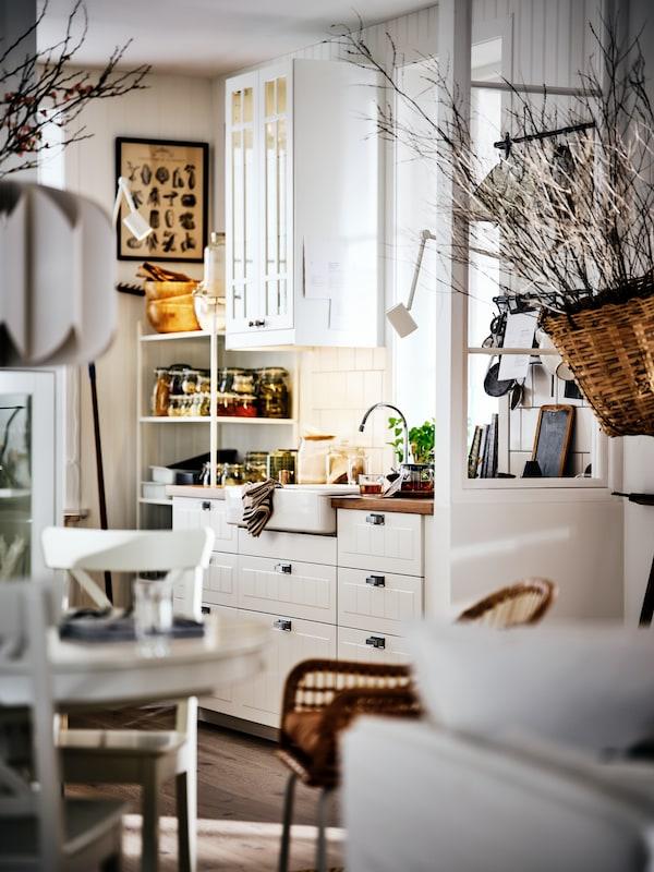 Une cuisine-salle à manger blanche et lumineuse de style campagnard, avec des armoires blanches, une table ronde et des branches séchées pour la déco.