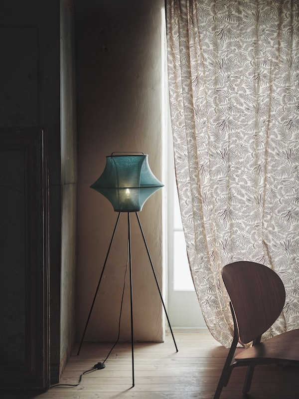 A lamp of unique futuristic design on three long legs, covered in green fabric, by a window in a darkened room.