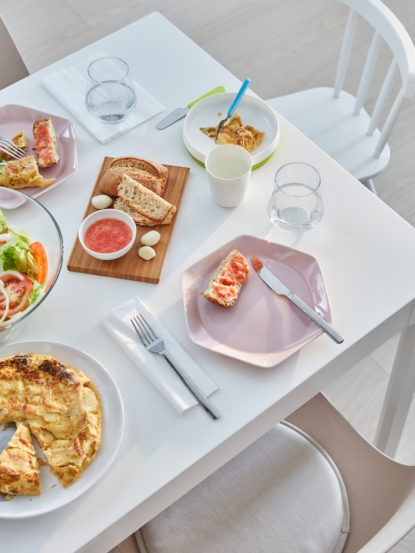 A white kitchen table set with pink plates, cutlery and drinking glasses, and a salad and an omelette on serveware.