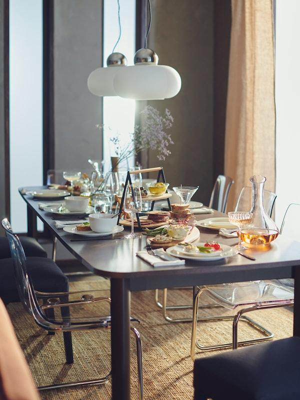 Une salle à manger moderne. Une table à rallonge STRANTORP foncée et de la vaisselle blanche.