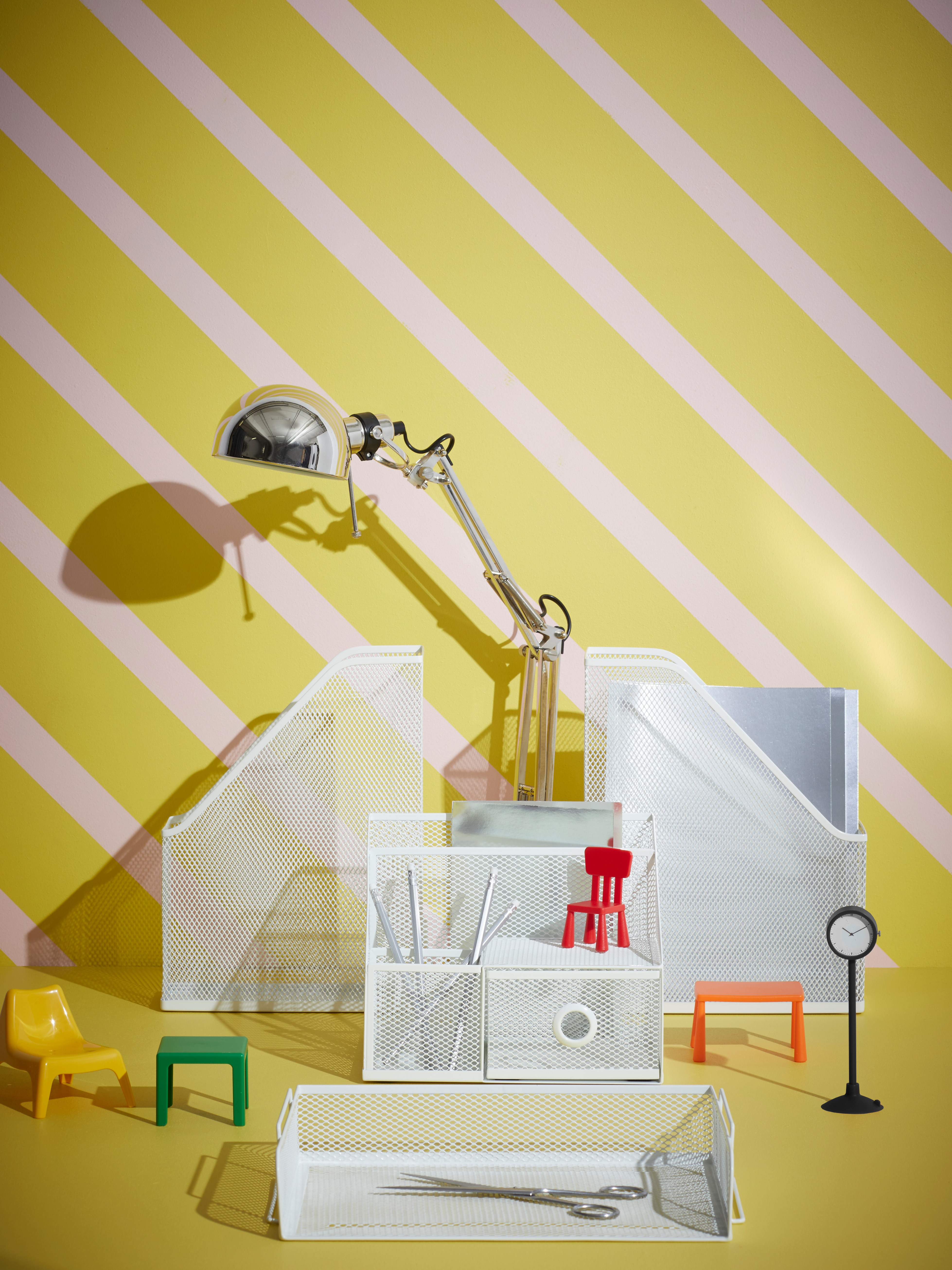 DRÖNJÖNS white steel desk organisers arranged on a yellow and pink striped background with a work lamp and toy furniture.