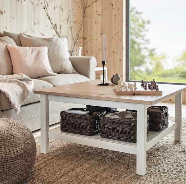 Sofa azul con cojines con diseño negro y blanco, del modelo de IKEA GLOSTAD. Se encuentra en una sala con piso de madera y una mesa blanca IKEA TINGBY, sobre una alfombra TIPHEDE de color gris.