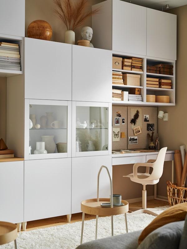Un salon bien rangé avec un rangement modulaire BESTÅ blanc, un poste de travail, une chaise pivotante et des étagères remplies de livres et de boîtes.