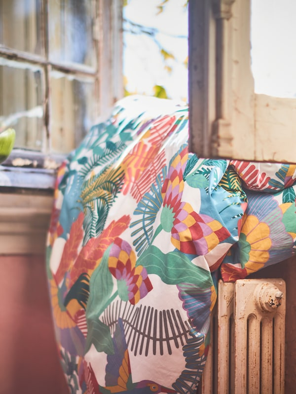 An open window with a duvet in a colorful SKOGSFIBBLA quilt cover draped over the windowsill and on top of a radiator.