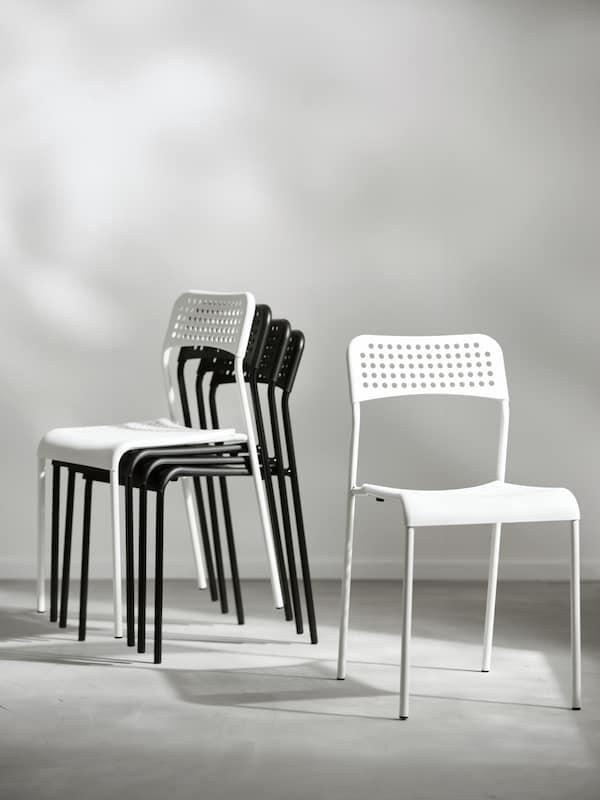Na sebe položené tri čierne ajedna biela stolička ADDE ajedna osamotená biela stolička ADDE, otočená smerom od nich.