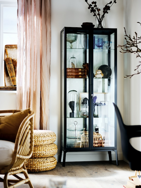A black MILSBO cabinet with glass doors filled with an assortment of objects, in the corner of a bright living room.