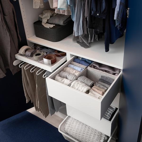 Et åbent PAX garderobeskab med hvidt stel og hvide skuffer trukket lidt ud, så man kan se tøjer organiseret deri. Der er også buksebøjler med bukser på.