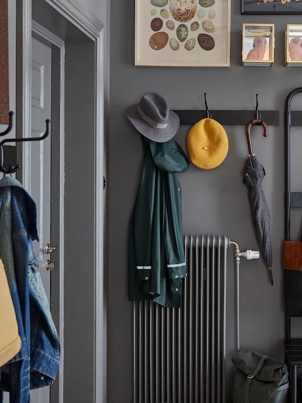 Un colgadoiro PINNIG con 3ganchos nunha parede gris a carón dunha porta, colocados sobre un radiador, dos que colgan chaquetas, sombreiros e un paraugas.