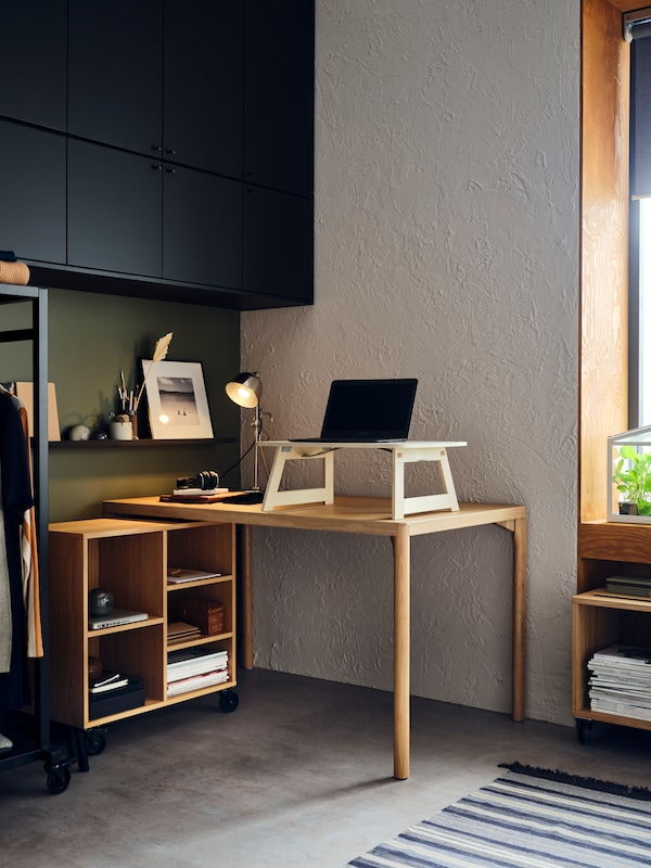A RÅVAROR table and shelving unit on castors are set up to create a desk area in a home. There is a laptop on the table.