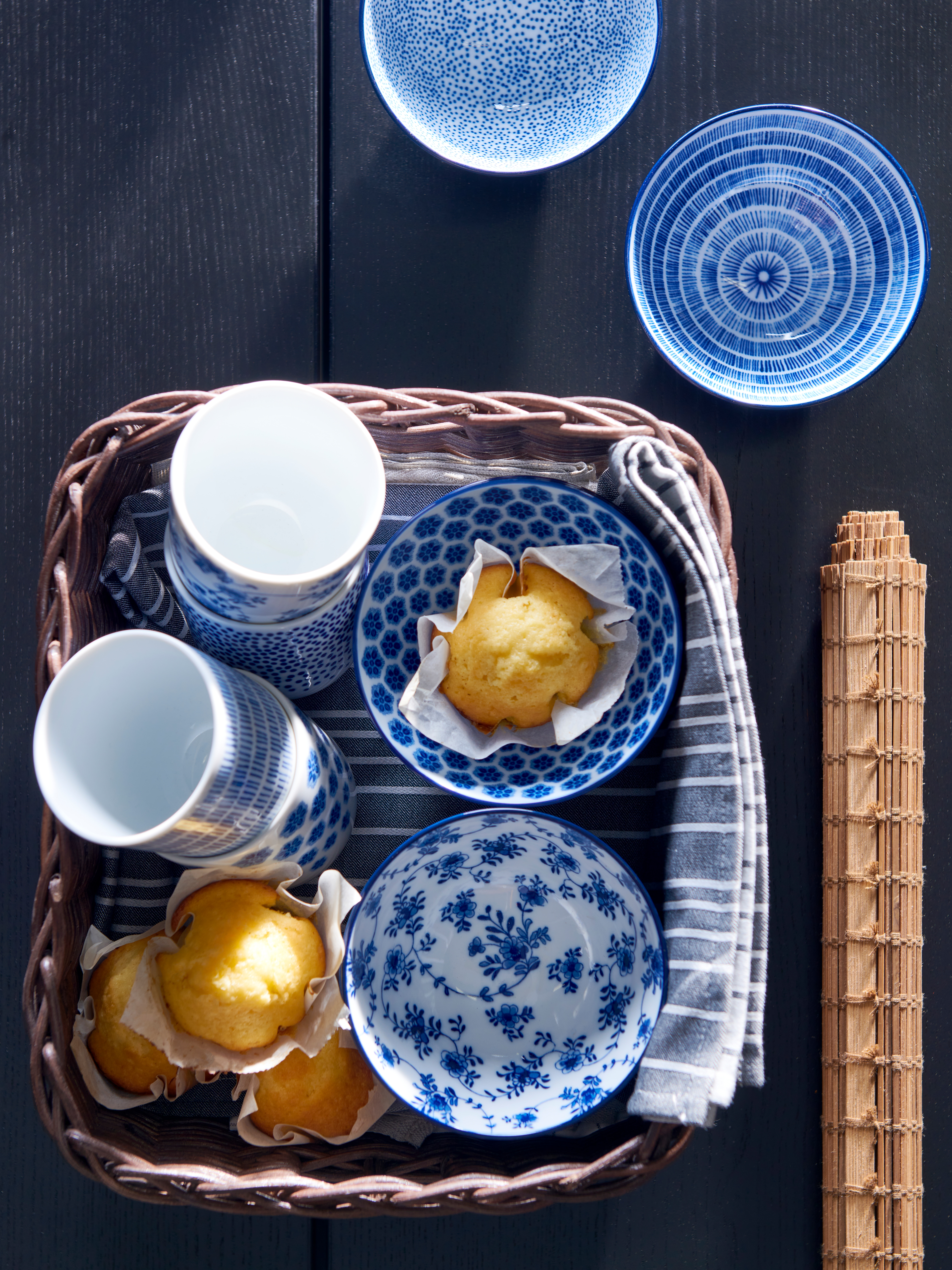 Table seen from above with a basket of four bowls and four cups with white and blue patterns, and a place mat next to it.