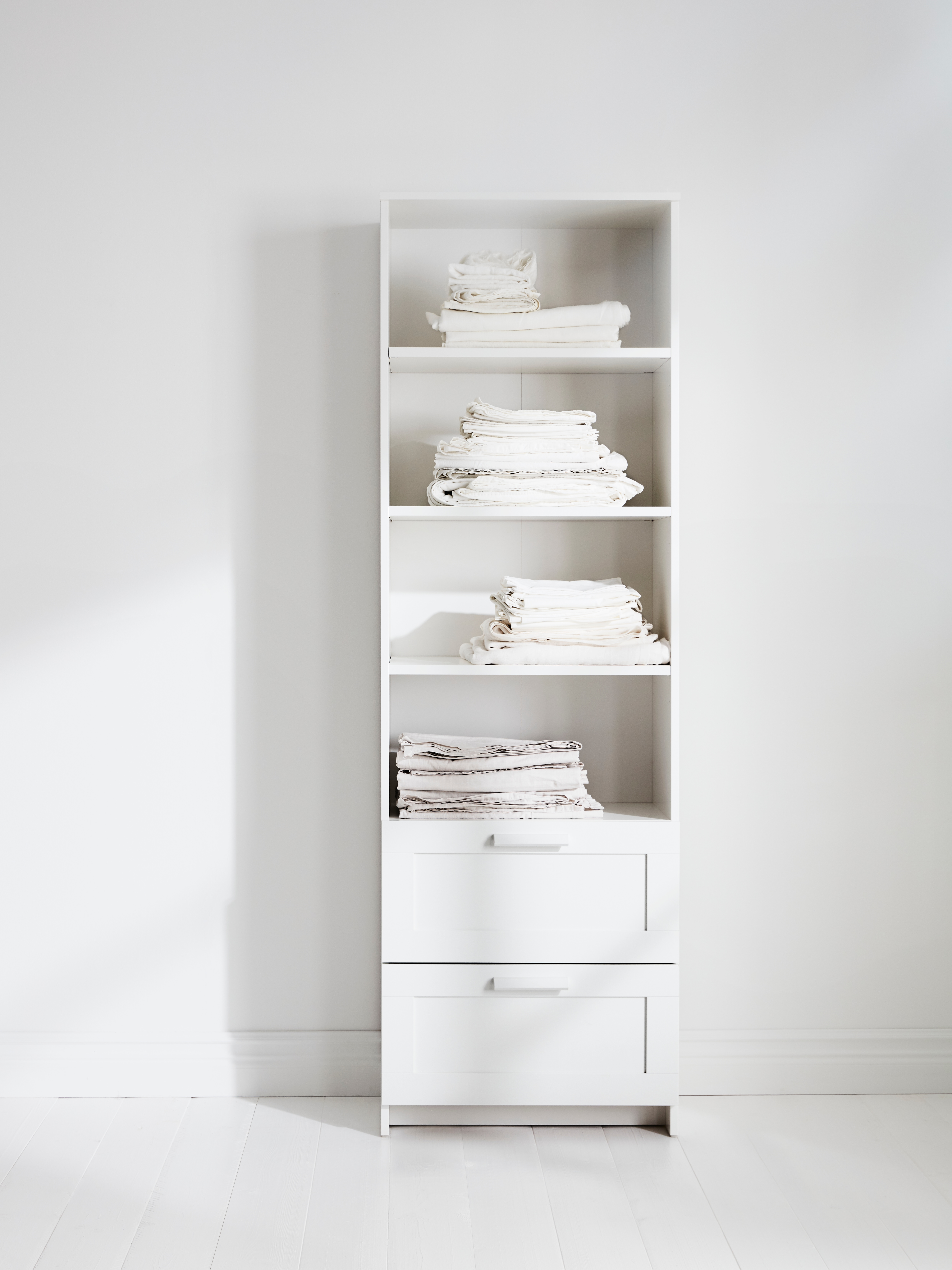 A white BRIMNES bookcase has two drawers and four shelves. It is against a white wall, holding stacks of folded white linens.