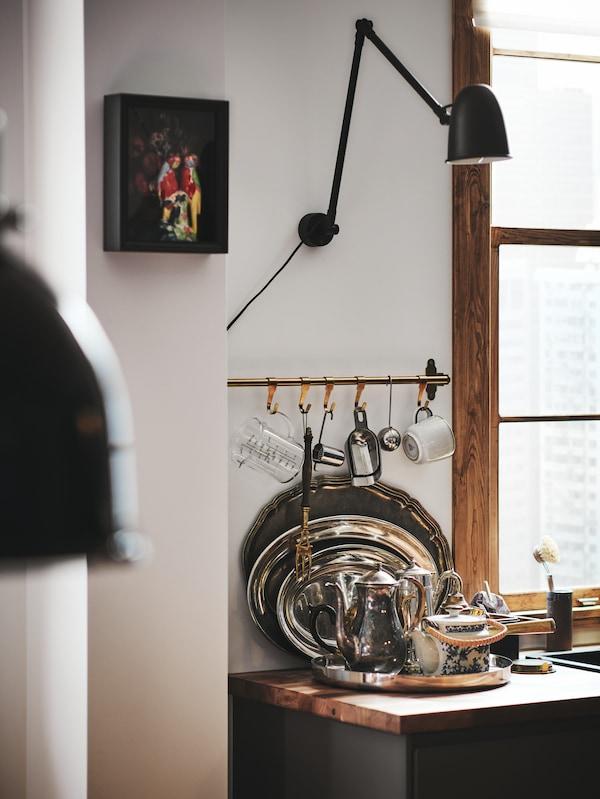 سطح عمل خشبي وفوقهصينية عليهاأواني فضية عتيقة. وفي الأعلى، توجد سكة تعليق للمطبخ تتدلى منها أدوات المطبخ.