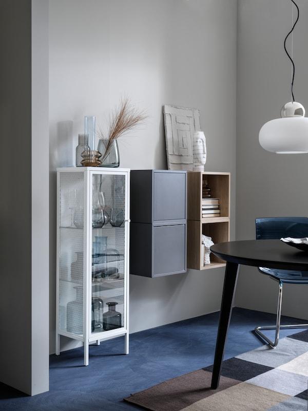 Une armoire BAGGEBO en métal/blanc aux portes vitrées dans une salle à manger à côté de deux armoires EKET fixées au mur.