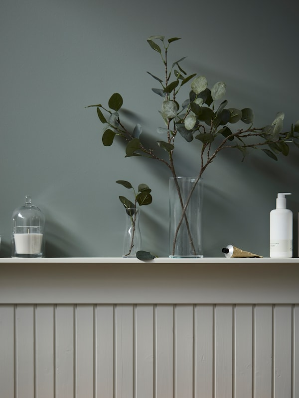 A half-panel wall with a shelf with a candle in a glass dome, and artificial olive twigs are displayed in glass vases.