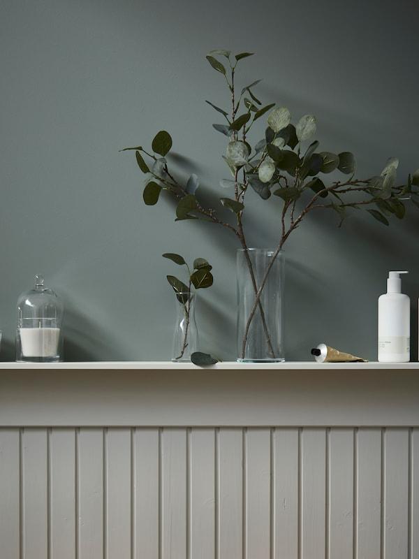 Mur revêtu d'un lambris à mi-hauteur, surmonté d'une étagère sur laquelle sont exposés une bougie sous une cloche en verre et des rameaux d'olivier artificiels dans des vases en verre.