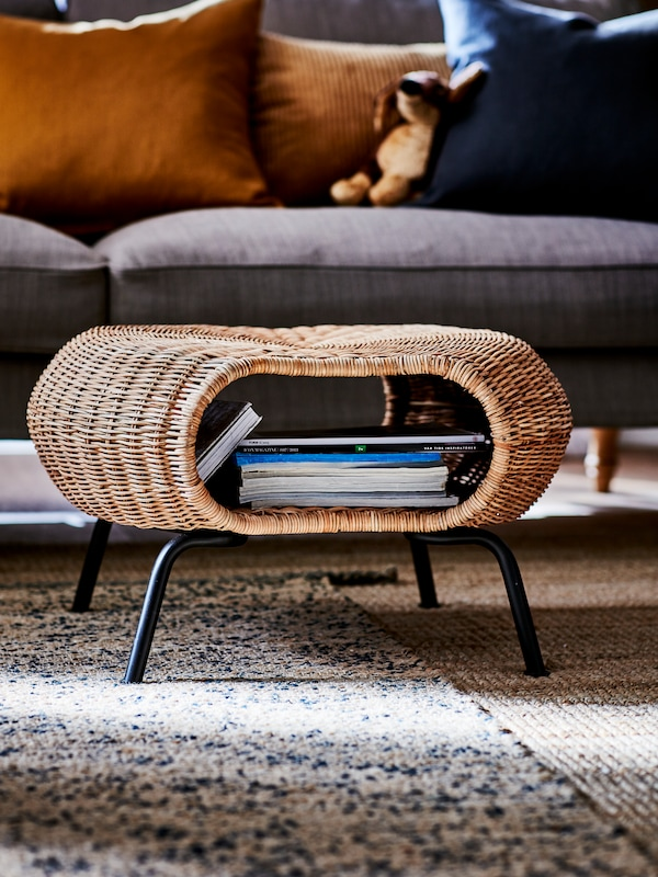 A rattan footstool with anthracite legs and books stored under the seat. A grey-beige sofa with cushions stands behind.