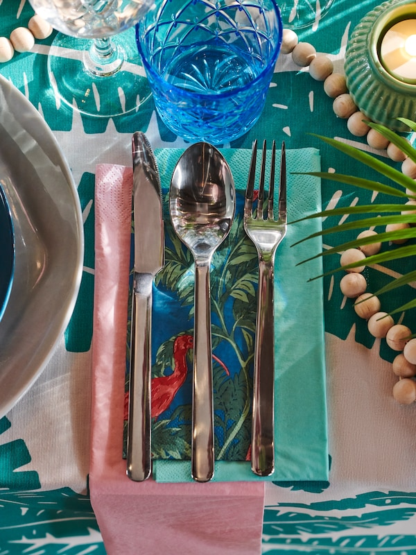 Knife, fork and spoon lying on a patchwork of SOMMARLIV and FANTASTISK paper napkins as parts of a festive table setting.