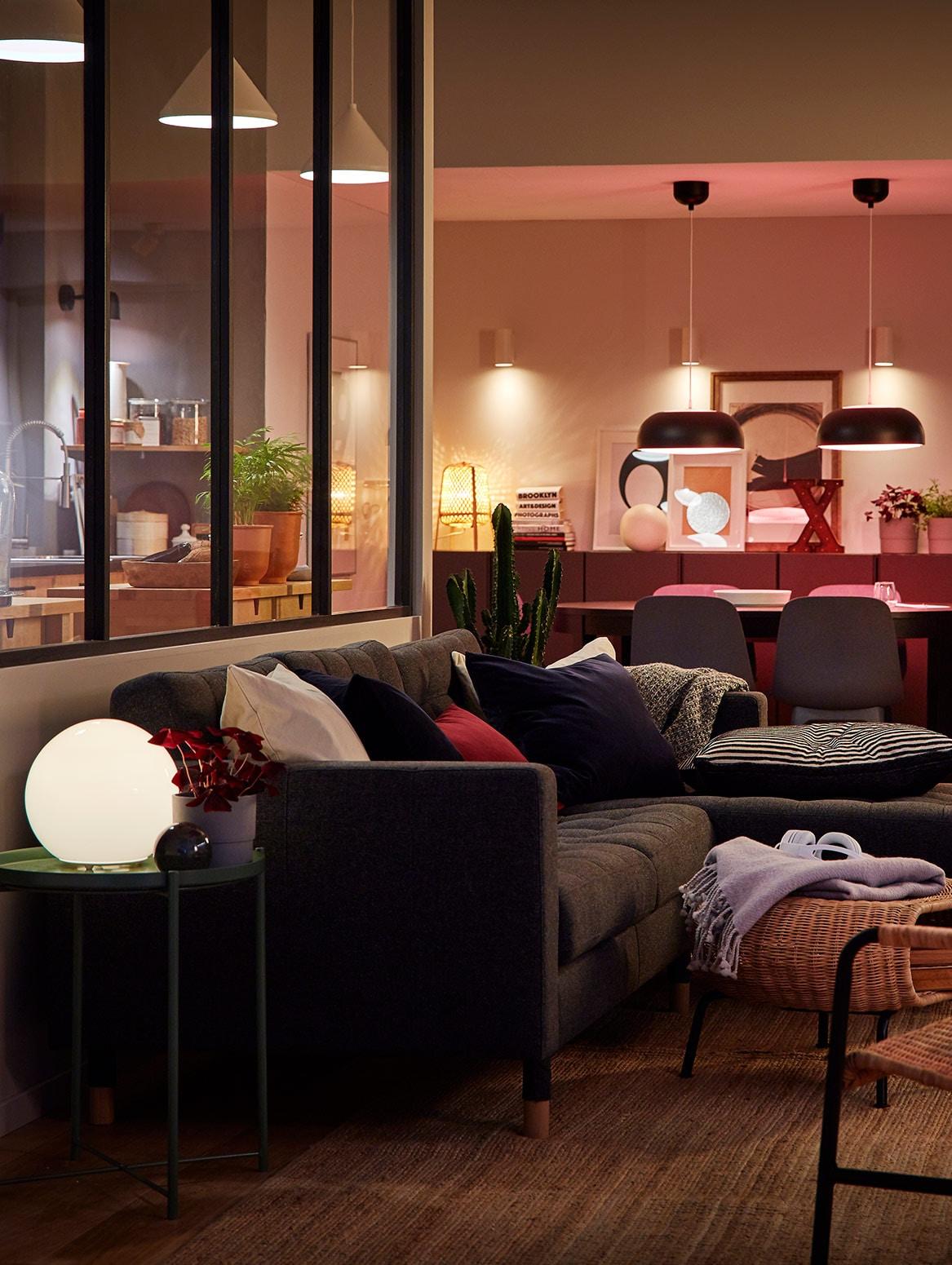 Гостиная: диван с декоративными подушками, стол со стульями, подвесные светильники и настольные лампы.