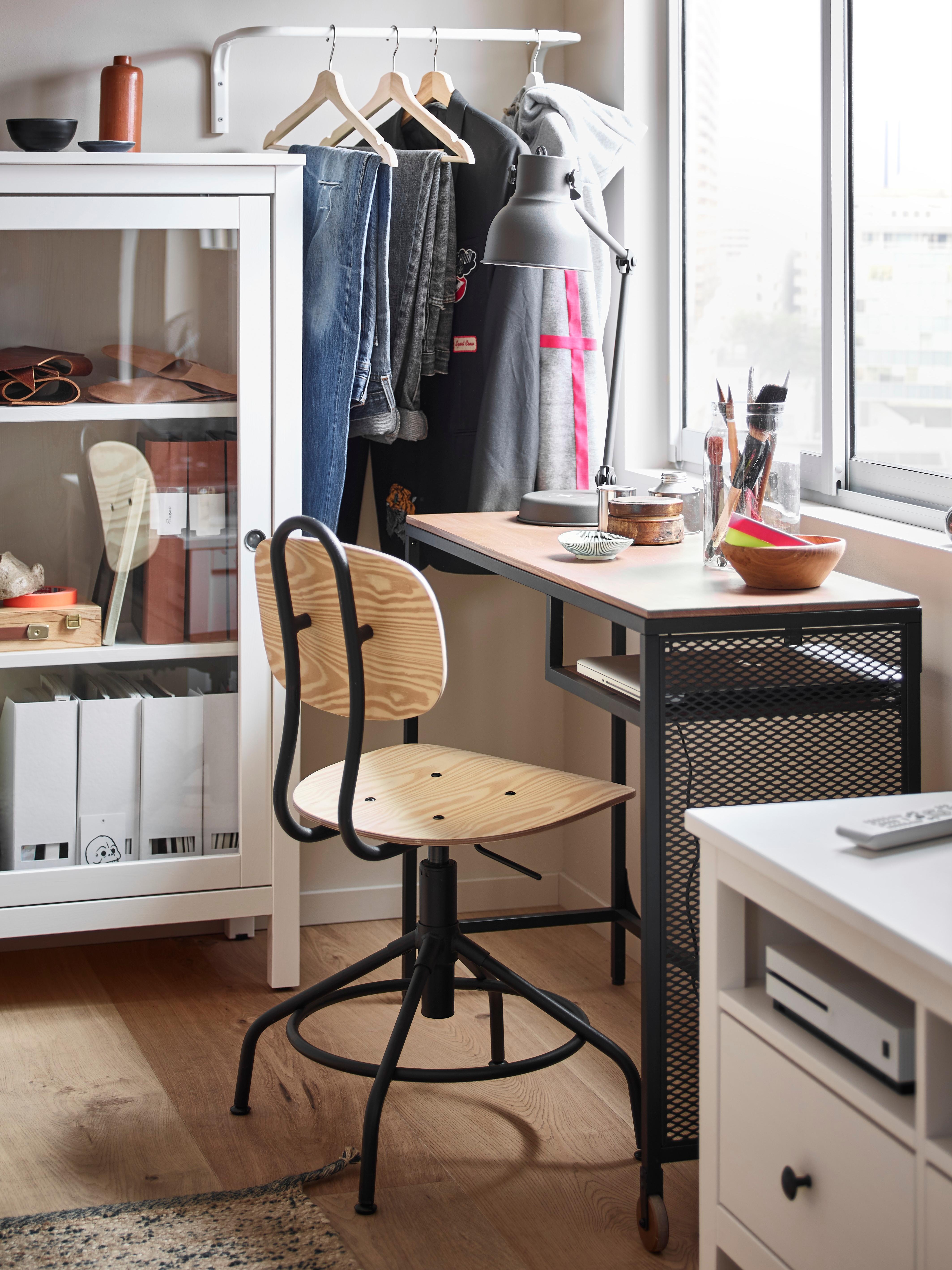 Schreibtisch mit einem KULLABERG Drehstuhl in Kiefer/Schwarz, der im Industriestil gehalten ist; Sitz und Rückenlehne sind aus Holz und das Gestell aus Metall. Der Tisch steht unter einem Fenster neben einer Glasvitrine mit Akten.
