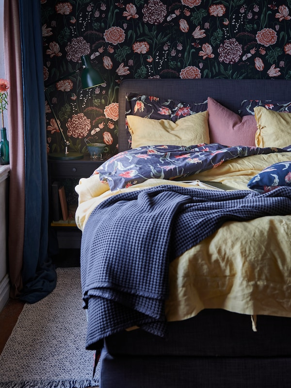 A DUNVIK duvan bed with light yellow PUDERVIVA bed linen and a VÅRELD bedspread stands against a wall with floral wallpaper.