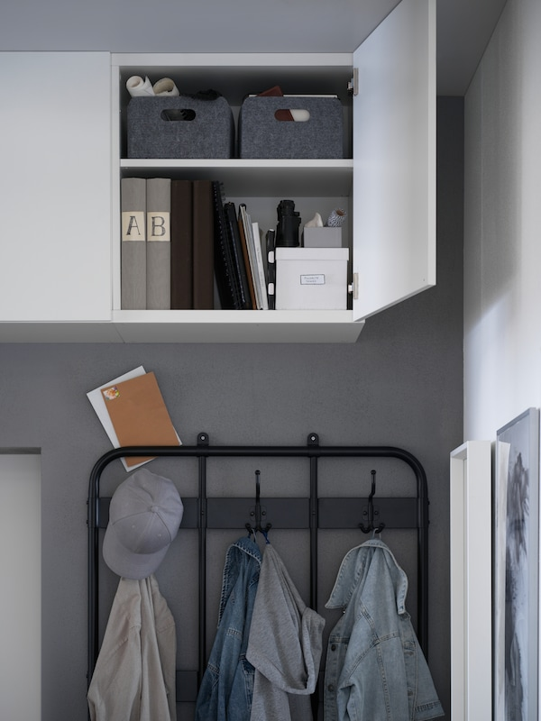 White BESTÅ storage units mounted above a coat rack, with one door open with files and boxes inside.