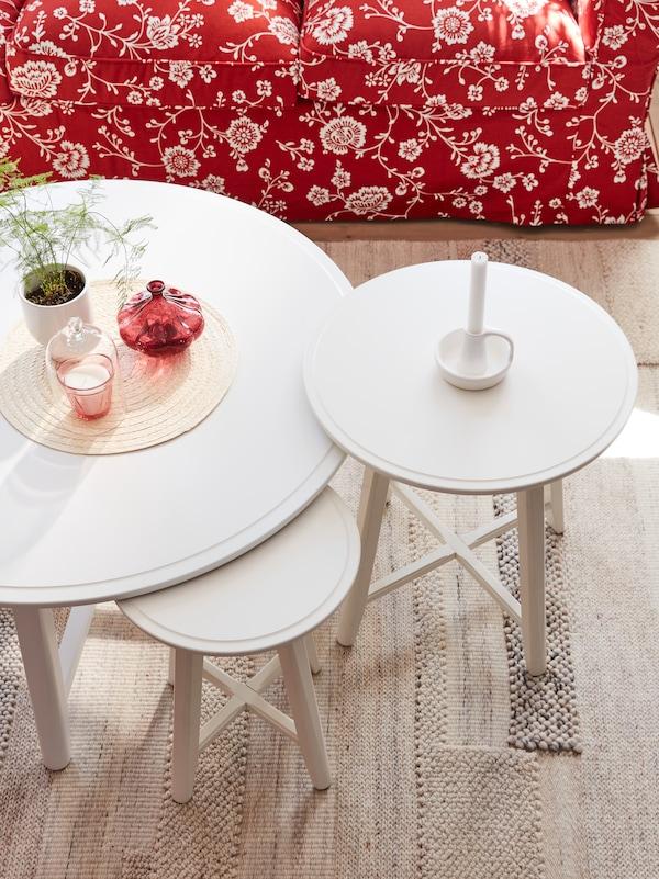 Runde weiße Beistelltische, auf denen ein Tischset mit einer kleinen Pflanze in einem Übertopf, ein Glas und andere Gegenstände zu sehen sind, steht auf einem Teppich in Beige.