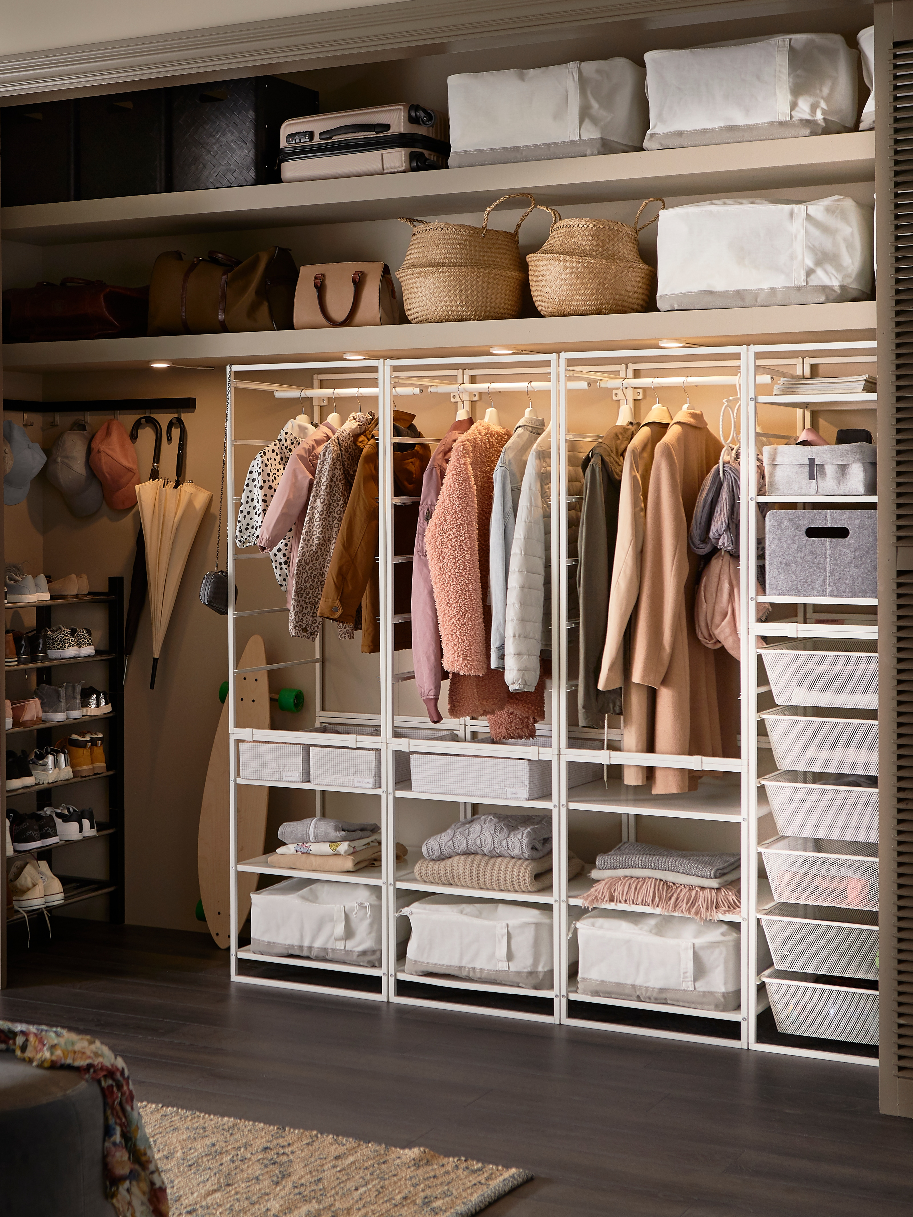 JONAXEL storage system with metal baskets containing clothes, and other articles of clothing hanging on racks.