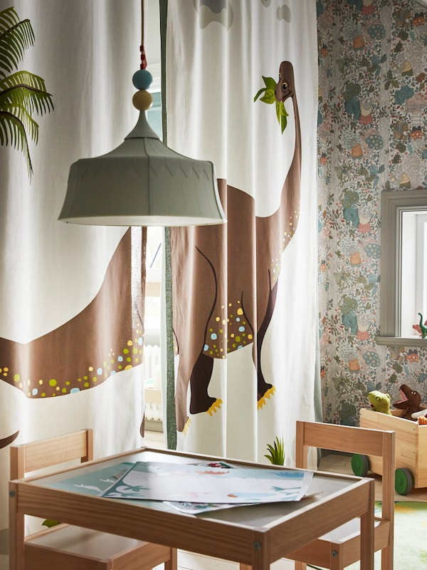 JÄTTELIK curtains with a LÄTT children's table and chairs in front, and a TROLLBO pendant lamp hanging over the table.