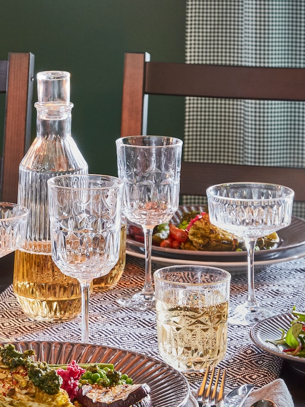 A set table with two SÄLLSKAPLIG wine glasses, one champagne coupe and one drinking glass and a carafe.