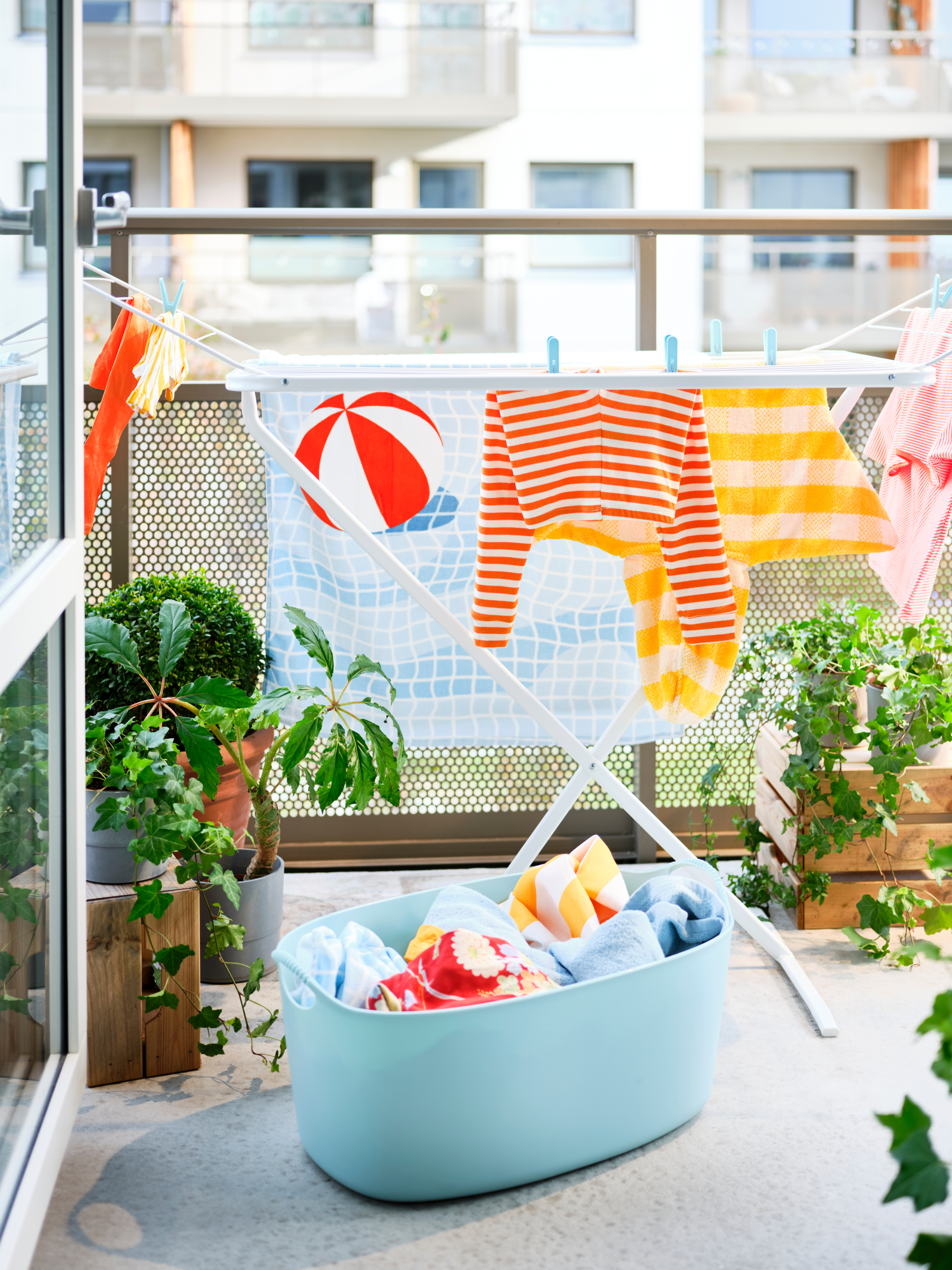 A blue TORKIS flexi laundry basket filled with laundry and a MULIG drying rack on a sunny balcony decorated with plants.