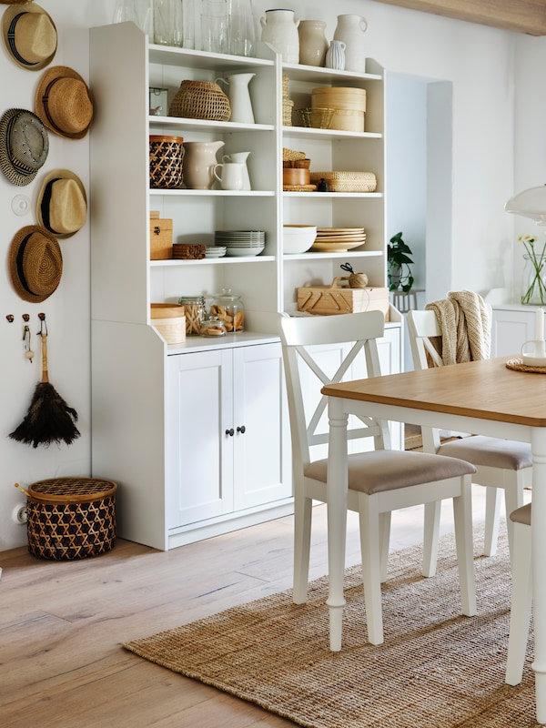 Two white HAUGA high cabinets by a dining table, with dinnerware, jugs and vases on the shelves. Hats hang on the wall nearby.