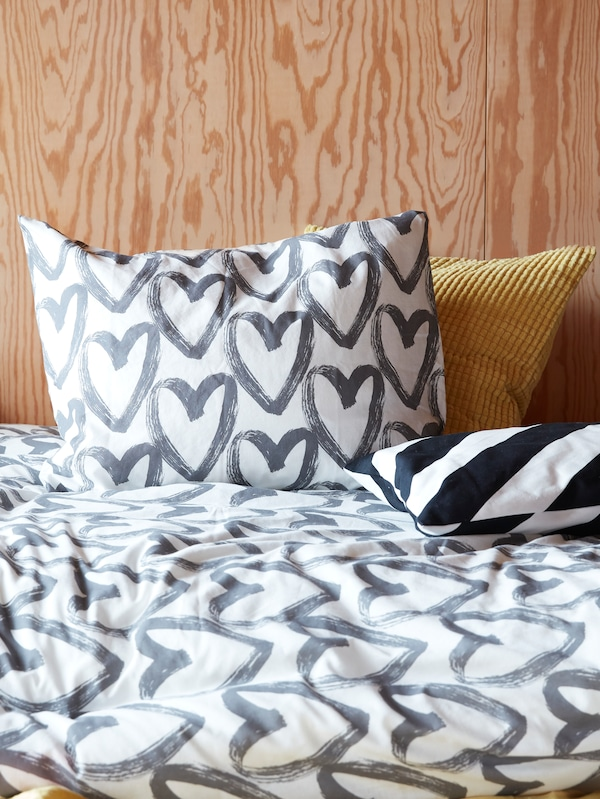 A bed with two cushions and a LYKTFIBBLA quilt cover and pillow case with gray hearts on a white background.