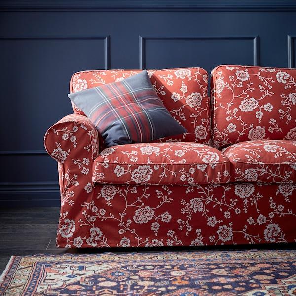 Ein rotes Sofa mit weißem Blumenmuster steht vor einer blauen Wand. Auf ihm liegt ein Kissen, davor befindet sich ein Teppich.