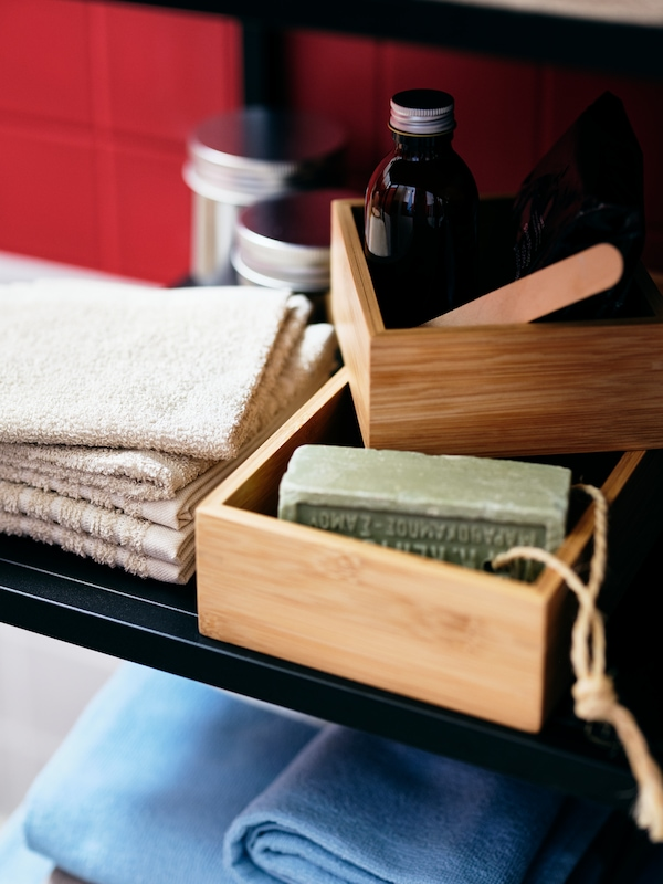 Folded towels, jars and bottles, and bathroom accessories in a pair of TAVELÅN trays share a shelf of an ENHET cabinet.