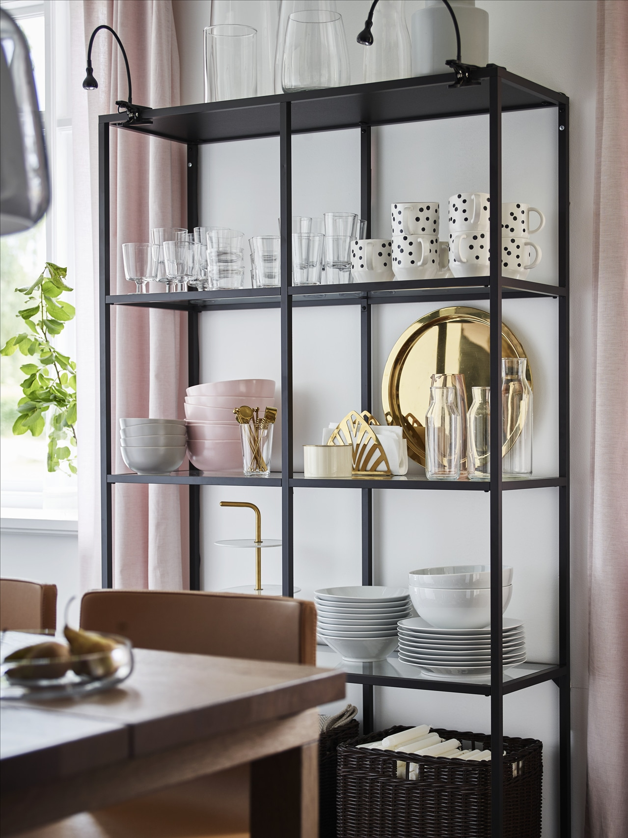 A dining room wall with a black-brown VITTSJÖ shelving unit holding glass and porcelain tableware, and a table with chairs.