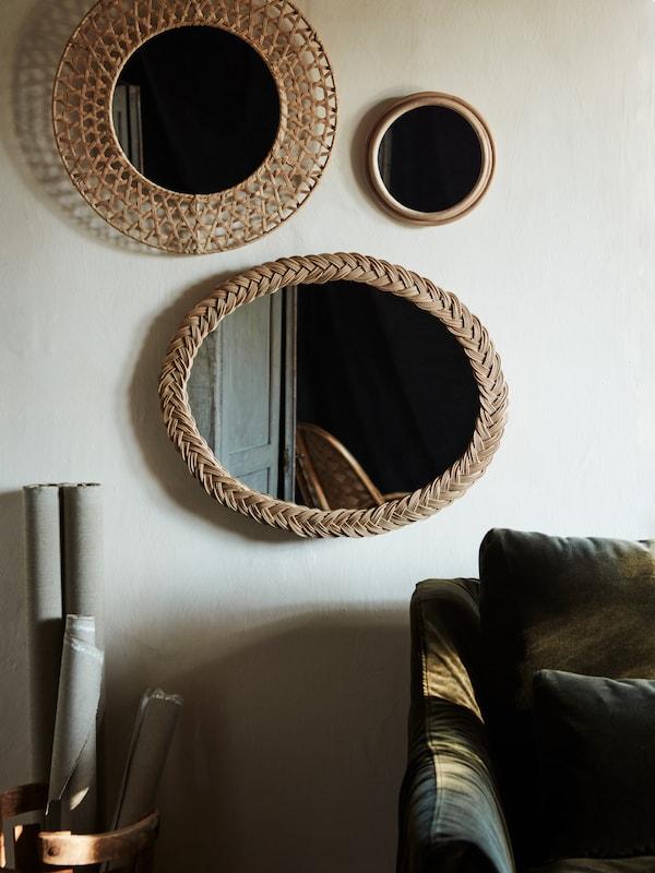 Ein ovaler KRISTINELUND Spiegel mit einem Rahmen aus dekorativ verwobenem Rattan hängt an einer grauen Wand; daneben hängen zwei kleinere runde Spiegel mit gewebtem Rahmen.