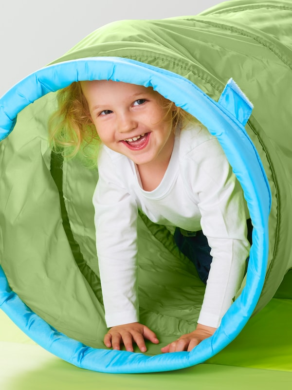 A smiling child in a white top coming out of a green BUSA play tunnel placed on a green mat.