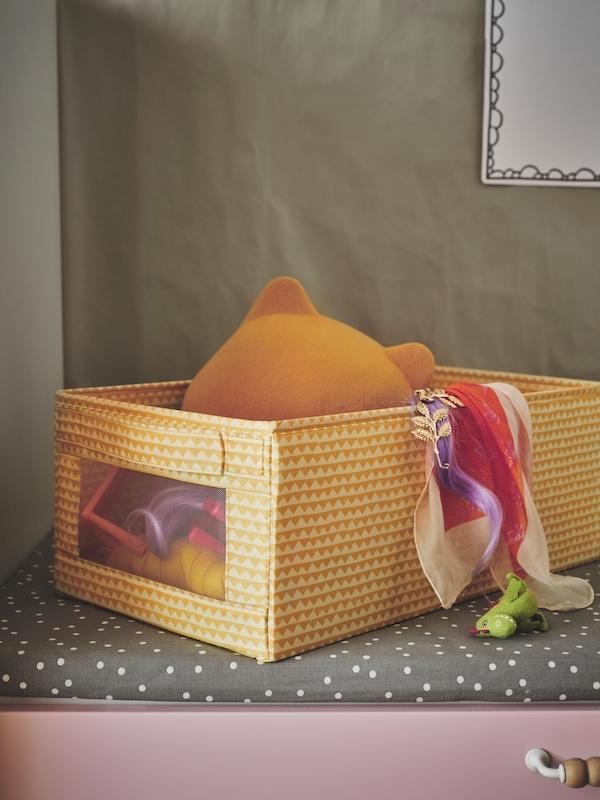 Eine gelbe UPPRYMD Box mit Spielzeug steht auf einer grauen BÄNKKAMRAT Bankauflage; darunter befindet sich eine Schublade in Rosa.