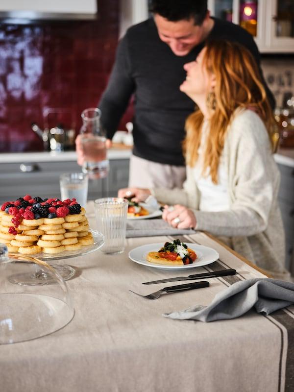 Dva lidé u kuchyňského ostrůvku s ubrusem a sklenicemi VARDAGEN, jídlem na talířích a skleněným servírovacím stojanem ARV BRÖLLOP.