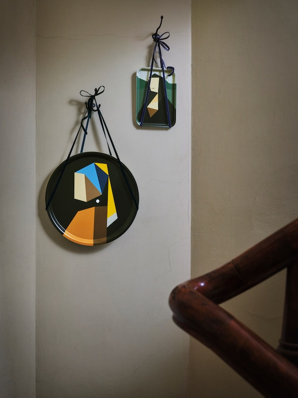 Two DEKORERA trays, with reworked da Vinci and Vermeer motifs, are hung with string side by side on a light brown wall.